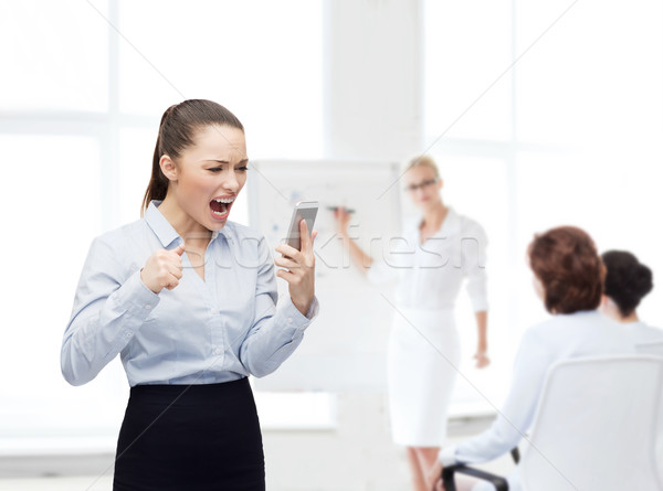 screaming businesswoman with smartphone Stock photo © dolgachov
