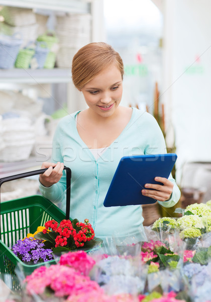 woman with tablet pc and basket at flower shop Stock photo © dolgachov
