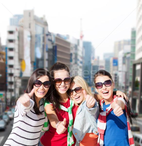 happy teenage girls showing thumbs up at city Stock photo © dolgachov