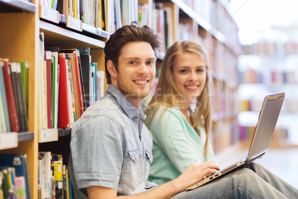 happy students with laptop in library Stock photo © dolgachov
