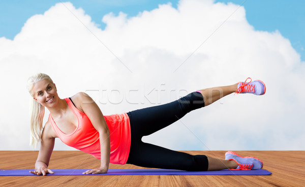 smiling woman exercising on mat over floor and sky Stock photo © dolgachov