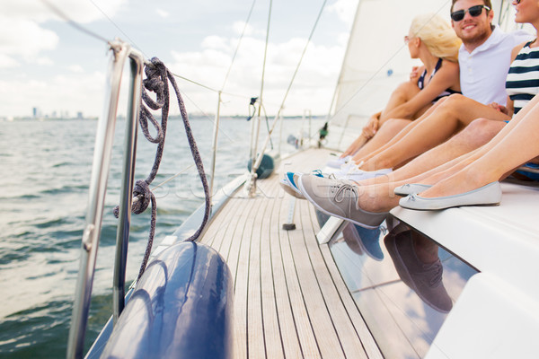 close up of friends legs sitting on yacht deck Stock photo © dolgachov