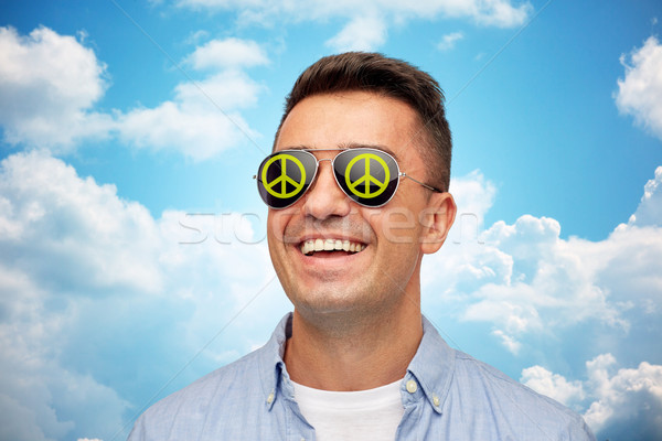 face of smiling man in green peace sunglasses Stock photo © dolgachov