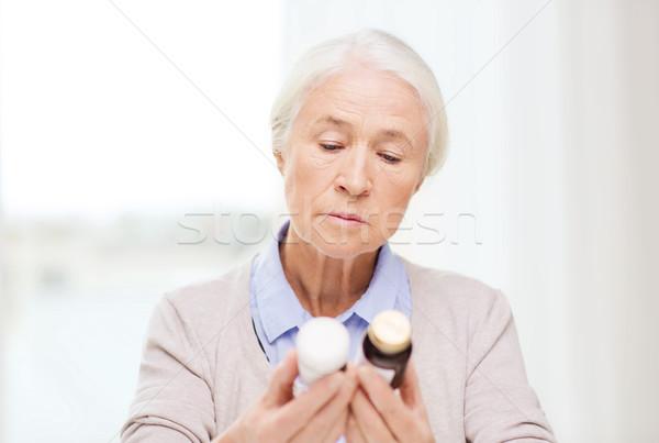 senior woman with medicine jars at home Stock photo © dolgachov
