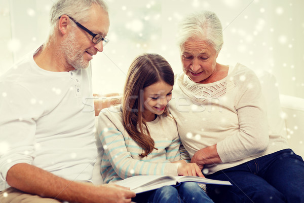 smiling family with book at home Stock photo © dolgachov