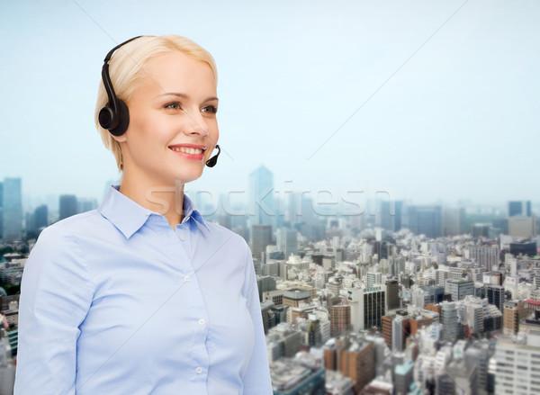 helpline operator in headset over city background Stock photo © dolgachov