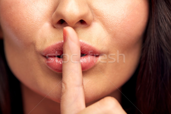 close up of young woman holding finger on lips Stock photo © dolgachov