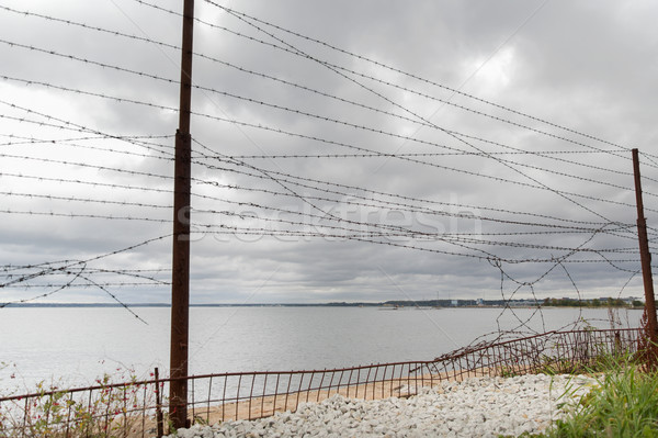 barb wire fence over gray sky and sea Stock photo © dolgachov