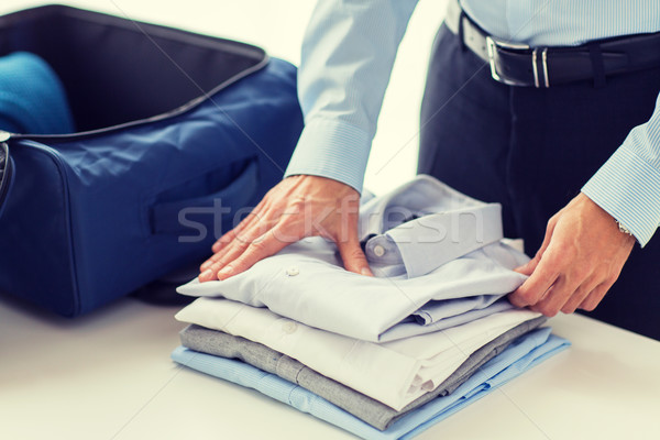businessman packing clothes into travel bag Stock fotó © dolgachov