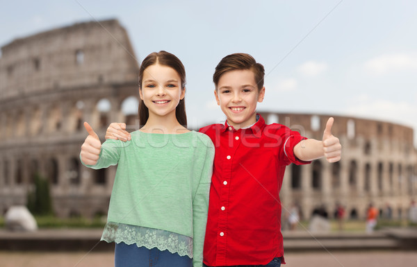 happy boy and girl showing thumbs up over coliseum Stock photo © dolgachov