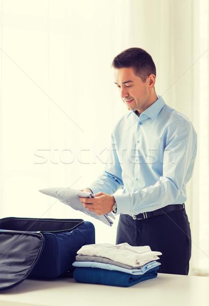 businessman packing clothes into travel bag Stock fotó © dolgachov