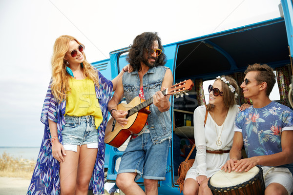 happy hippie friends playing music over minivan Stock photo © dolgachov