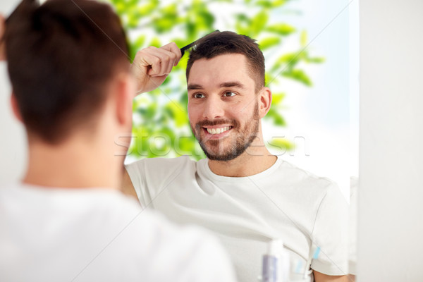 happy man brushing hair with comb at bathroom Stock photo © dolgachov