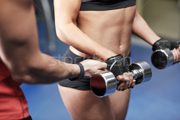woman with dumbbells flexing muscles in gym Stock photo © dolgachov