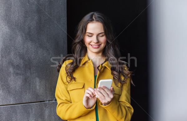 Mosolyog fiatal nő lány sms chat okostelefon technológia Stock fotó © dolgachov