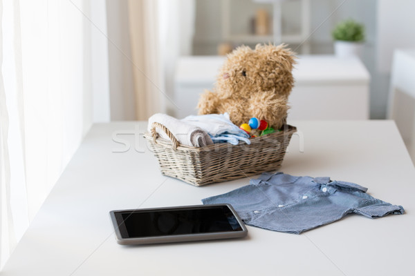 Stock photo: close up of baby clothes, toys and tablet pc