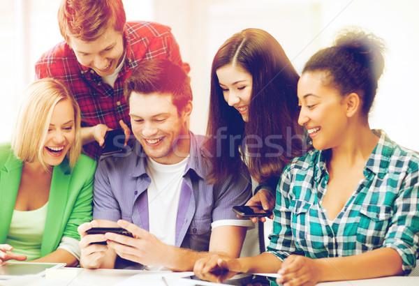 Foto d'archivio: Studenti · guardando · smartphone · scuola · istruzione · tecnologia