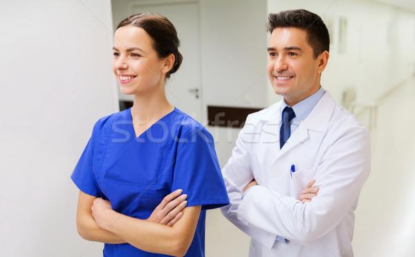 smiling doctor in white coat and nurse at hospital Stock photo © dolgachov
