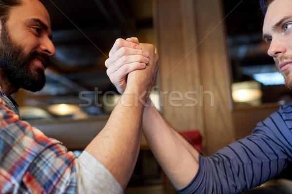 close up of men arm wrestling at bar or pub Stock photo © dolgachov