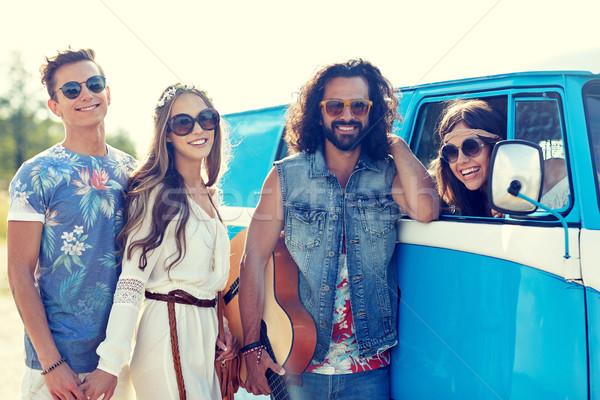 happy hippie friends with guitar over minivan car Stock photo © dolgachov