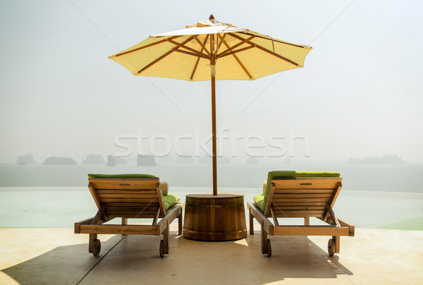 infinity pool with parasol and sun beds at seaside Stock photo © dolgachov