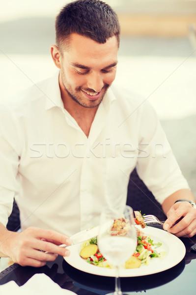happy man eating salad for dinner at restaurant Stock photo © dolgachov