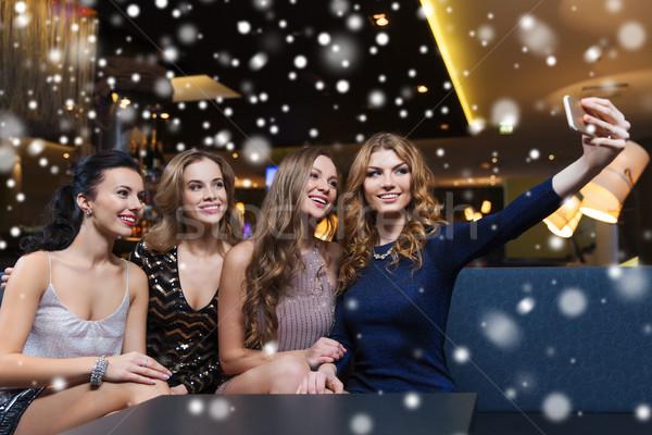 women with smartphone taking selfie at night club Stock photo © dolgachov