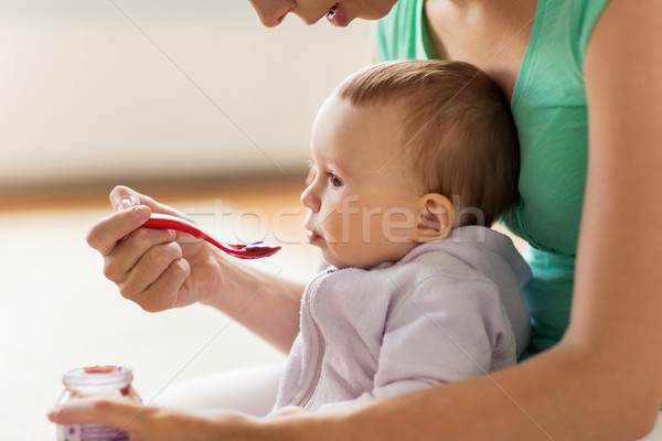 mother with spoon feeding little baby at home Stock photo © dolgachov