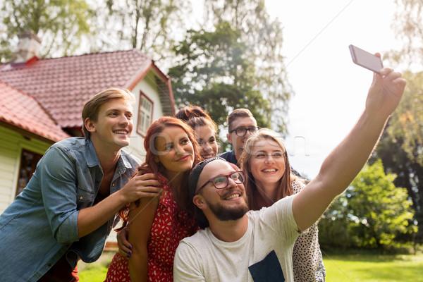 friends taking selfie at party in summer garden Stock photo © dolgachov