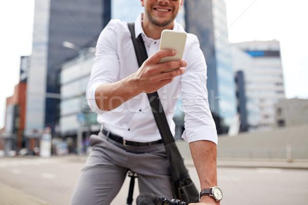 Férfi okostelefon fix viselet bicikli utca Stock fotó © dolgachov