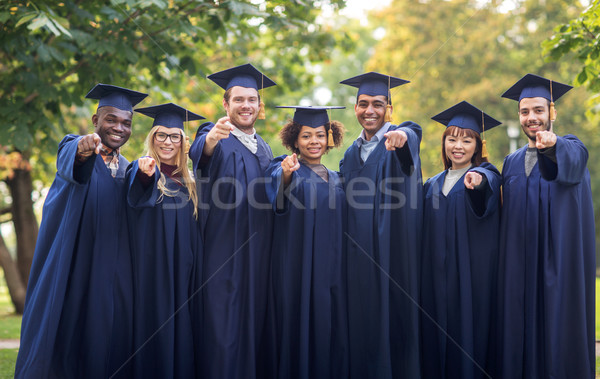 happy students or bachelors pointing finger at you Stock photo © dolgachov