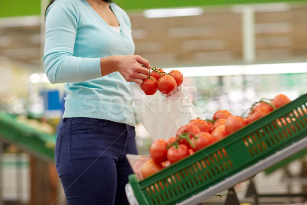 woman with bag buying tomatoes at grocery store Stock photo © dolgachov