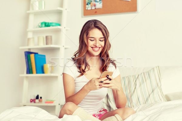 happy woman or girl with smartphone in bed at home Stock photo © dolgachov