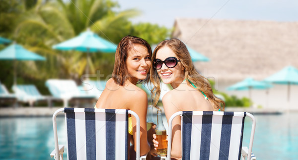 happy young women with drinks sunbathing on beach Stock photo © dolgachov