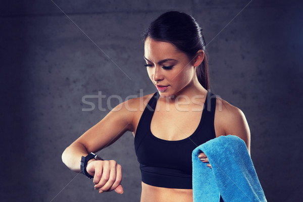 young woman with heart-rate watch and towel in gym Stock photo © dolgachov