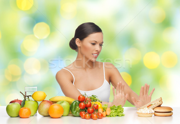 woman with fruits rejecting fast food on table Stock photo © dolgachov