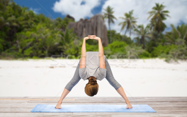 woman doing yoga wide-legged forward bend on beach Stock photo © dolgachov
