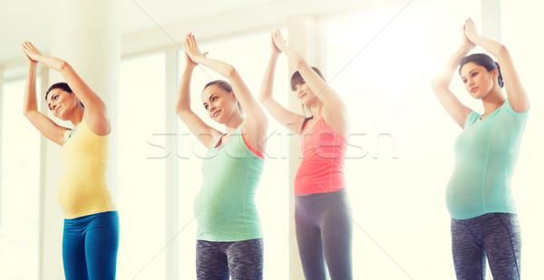 happy pregnant women exercising in gym Stock photo © dolgachov