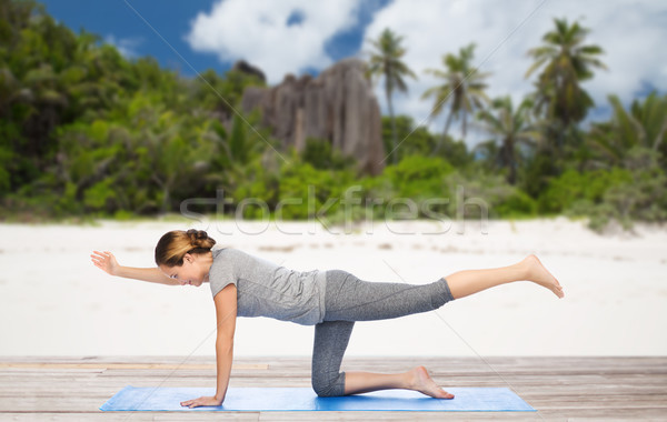 woman doing yoga in balancing table pose on beach Stock photo © dolgachov
