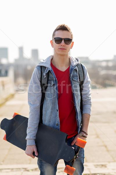 happy young man or teenage boy with longboard Stock photo © dolgachov