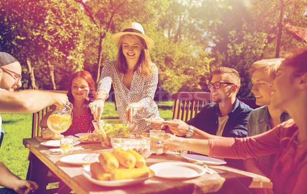 Stock photo: happy friends having dinner at summer garden party