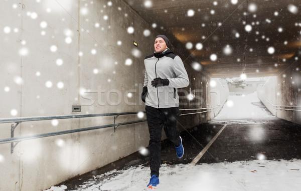 Happy Man Running Along Subway Tunnel In Winter Stock Photo