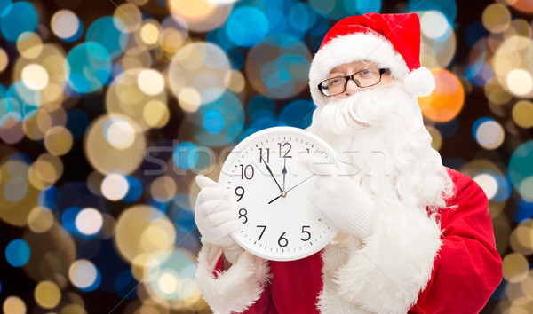 santa claus with twelve on clock at christmas Stock photo © dolgachov