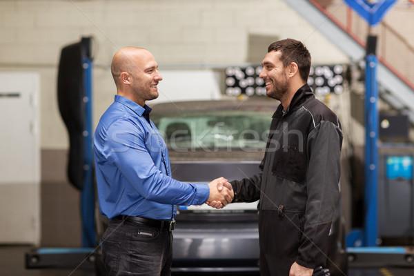 mechanic and customer shaking hands at car service Stock photo © dolgachov