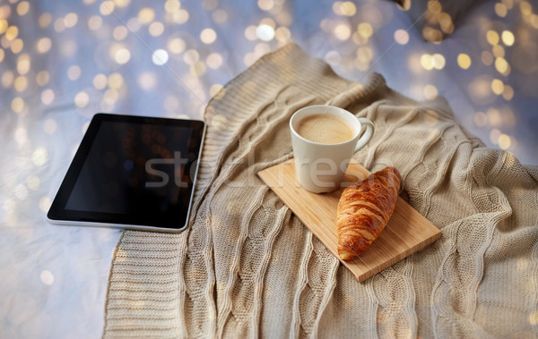 tablet pc, coffee and croissant on bed at home Stock photo © dolgachov