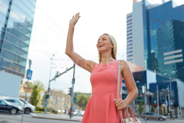 happy young woman waving hand on city street Stock photo © dolgachov