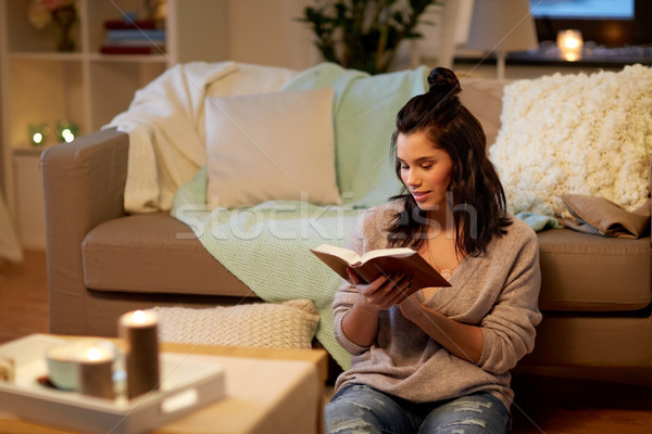 happy young woman reading book at home Stock photo © dolgachov