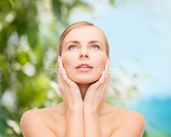 beautiful woman touching her face and looking up Stock photo © dolgachov