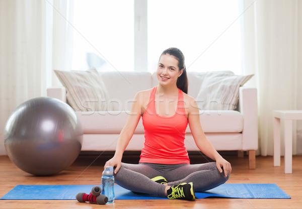Uśmiechnięty dziewczyna posiedzenia sprzęt sportowy fitness domu Zdjęcia stock © dolgachov