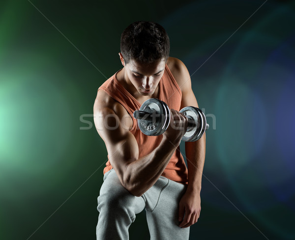young man with dumbbell flexing biceps Stock photo © dolgachov